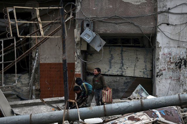 Children play near damaged buildings in the town of Douma, eastern Ghouta in Damascus, Syria January 5, 2016. Picture taken January 5, 2016. (Photo by Bassam Khabieh/Reuters)