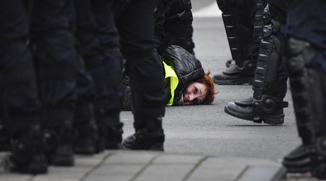 A woman in a yellow vest is detained by police during a demonstration in Brussels, Saturday, December 8, 2018. Hundreds of police officers are being mobilized in Brussels Saturday, where yellow vest protesters last week clashed with police and torched two police vehicles. More than 70 people were detained. (Photo by Geert Vanden Wijngaert/AP Photo)