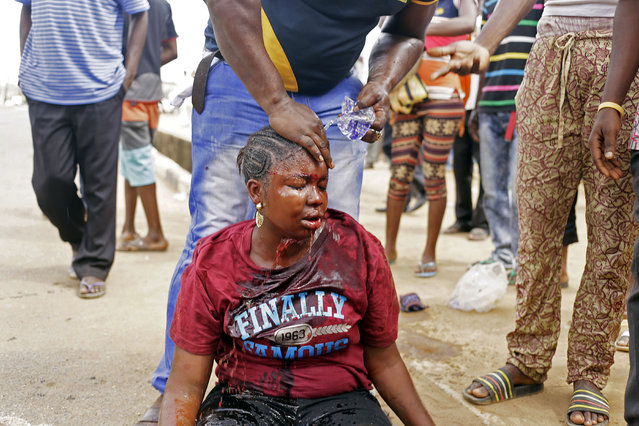 A man washes the face of a female voter that was beaten by a Nigerian policewoman at a poling station during an altercation. The police woman was later arrested for misconduct, in Lagos, Nigeria, Saturday, March 28, 2015. Millions of Nigerians turned out Saturday to vote in a presidential election that analysts say is too close to call between President Goodluck Jonathan and former military dictator Muhammadu Buhari. (Kunle Ogunfuyi/AP Photo)