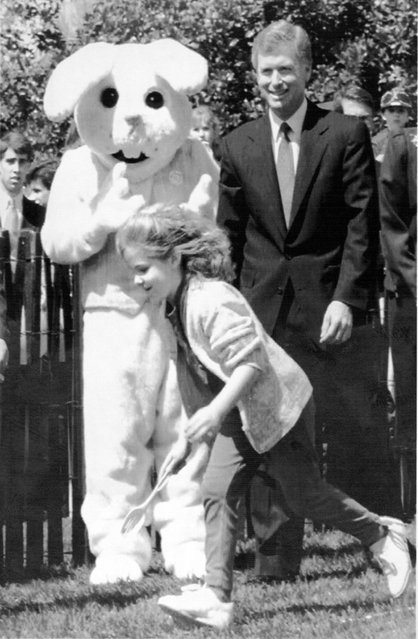 April 1, 1991 U.S. Vice President Dan Quayle (R) accompanied by giant bunny watch the Easter Egg Poll on the south grounds of the White house 1 April annual event held the Monday after Easter attracts thousands of area children. (Photo by J. David Ake/AFP Photo)