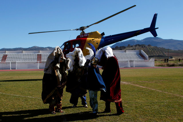 Men dressed up as the Three Wise Men and a woman (2nd R) as the Royal Mailman are buffeted by wind from the rotors of a helicopter after arriving on it to take part in the traditional Epiphany parade in Ronda, near Malaga, southern Spain January 5, 2017. (Photo by Jon Nazca/Reuters)