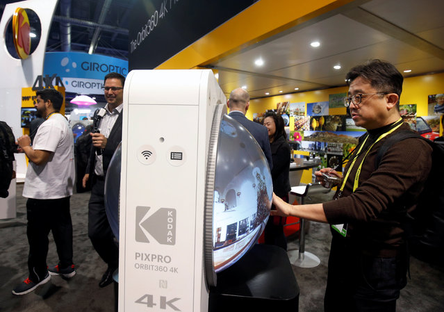 Patrick Lee (R) of Taiwan scrolls through 360 degree video on an oversized mock-up of a Kodak Pixpro Orbit 360 4K VR camera during the 2017 CES in Las Vegas, Nevada, U.S., January 6, 2017. The camera will be available in March or April and retail for about $500.00, a representative says. (Photo by Steve Marcus/Reuters)