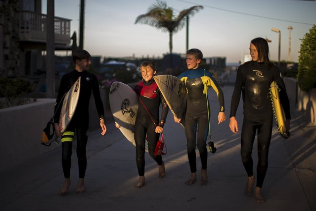Luke Personius, 12 (L-R), Shane Moseley, 13, Reid Inskeep, 13, and Sebastian Rodriguez, 13, walk home after surfing before school at sunrise in Hermosa Beach, California March 24, 2015. The group of friends surf at sunrise most mornings, then shower outside and walk to school. (Photo by Lucy Nicholson/Reuters)