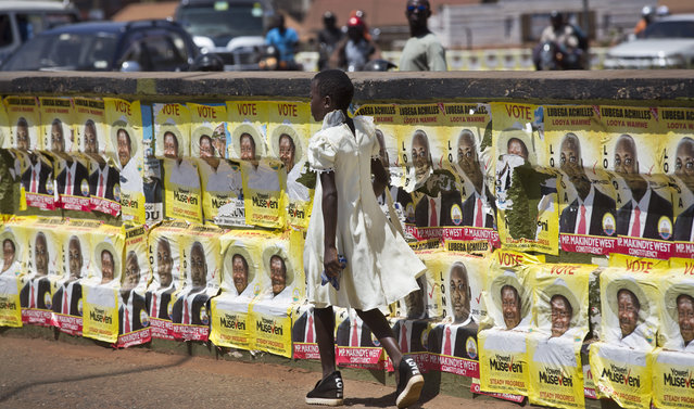 A girl walks past campaign posters for long-time President Yoweri Museveni, as well as for local members of Parliament, on a street in Kampala, Uganda Wednesday, February 17, 2016. On the eve of presidential elections, a heavy police and military presence could be seen in the capital Kampala. (Photo by Ben Curtis/AP Photo)