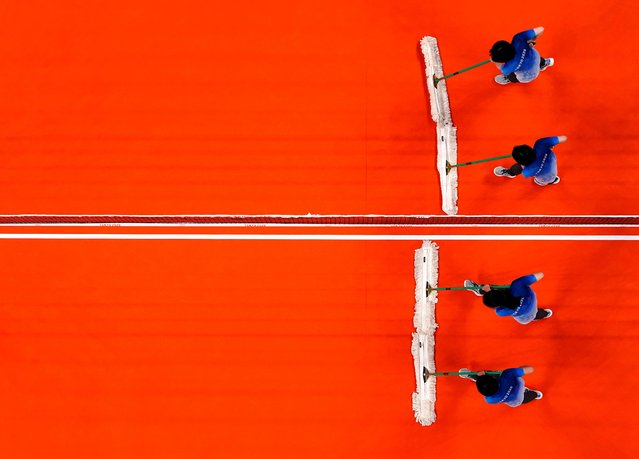 Staff members clean the court during the Women's Preliminary Round - Pool B volleyball match between China and Argentina on day ten of the Tokyo 2020 Olympic Games at Ariake Arena on August 2, 2021 in Tokyo, Japan. (Photo by Carlos Garcia Rawlins/Reuters)