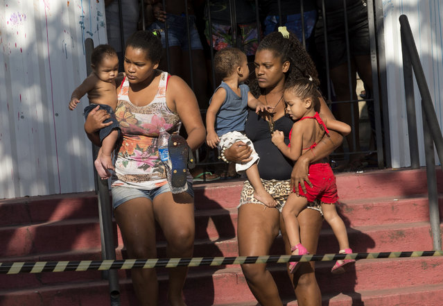 Women and children evacuate a building they invaded about a week ago in the Flamengo neighborhood of Rio de Janeiro, Brazil, Tuesday, April 14, 2015. (Photo by Silvia Izquierdo/AP Photo)