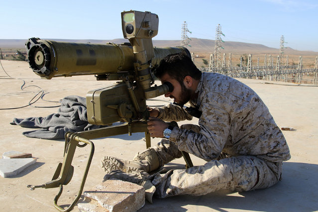 In this photo taken on Wednesday, February 17, 2016, a Syrian government soldier takes his position with an anti-tank rocket launcher, preparing to fire against Islamic State group positions in the province of Raqqa, Syria. (Photo by Alexander Kots/Komsomolskaya Pravda via AP Photo)