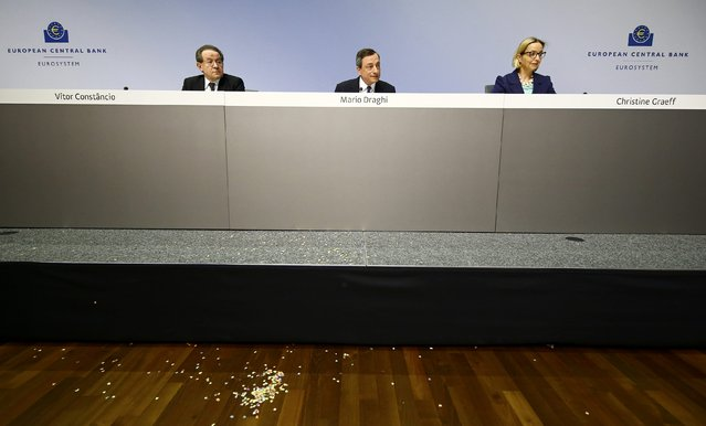 European Central Bank President Mario Draghi (C) speaks next to Christine Graeff, director general communications, and ECB Vice-President Vitor Constancio (L) at a news conference in Frankfurt, April 15, 2015. A woman protesting against European Central Bank policy leapt onto a desk in front of ECB President Mario Draghi on Wednesday as he spoke at a news conference, disrupting the normally technical presentation before she was carried away. (Photo by Kai Pfaffenbach/Reuters)
