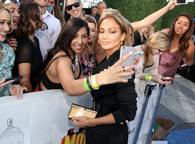 Jennifer Lopez takes a selfie with a fan as she arrives at the MTV Movie Awards at the Nokia Theatre on Sunday, April 12, 2015, in Los Angeles. (Photo by Matt Sayles/Invision/AP Photo)