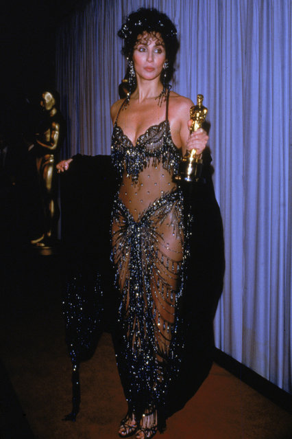 """American actor and singer Cher holds her Academy Award for Best Actress for her role in director Norman Jewison's film, """"Moonstruck"""", Shrine Civic Auditorium, Los Angeles, California on April 11, 1988. She wears an outfit designed by Bob Mackie. (Photo by Darlene Hammond/Getty Images)"""