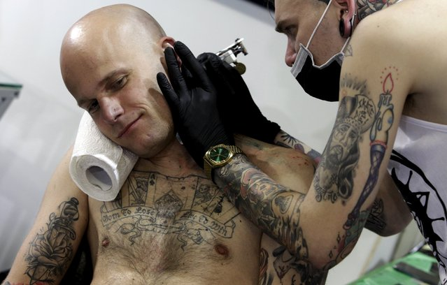 An artist draws a tattoo on a man's neck during a tattoo convention in Ljubljana April 18, 2015. (Photo by Srdjan Zivulovic/Reuters)