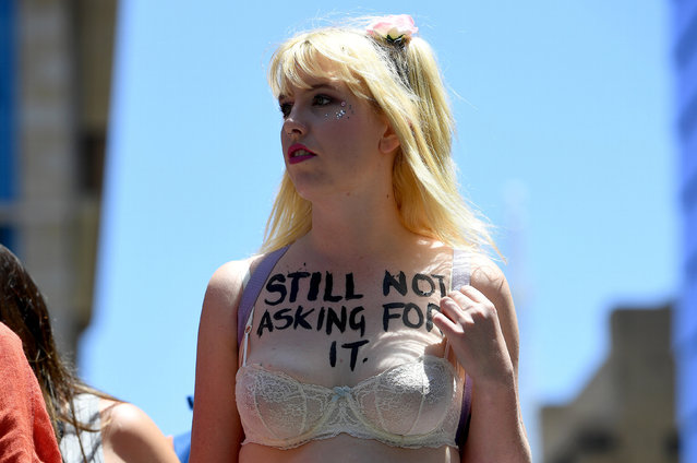 A protester wearing a bra and with a message written on her chest can be seen during the first of hundreds of womens' marches organized around the world in a show of disapproval of U.S. President Donald Trump in Sydney, Australia, January 21, 2017. (Photo by Dan Himbrechts/Reuters/AAP)