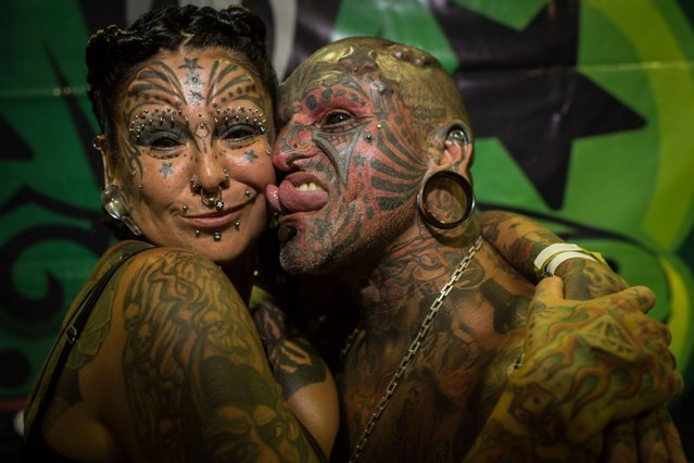Uruguayan tatoo artist Victor Hugo Peralta (R) and his wife, Argentinian tatoo artist Gabriela Peralta pose for a picture during the Tattoo Week Rio in Rio de Janeiro, Brazil, on January 5, 2014. Peralta and his wife Gabriela are registetered on the Guinnes World Records as the married couple with most body modifications. (Photo by Yasuyoshi Chiba/AFP Photo)