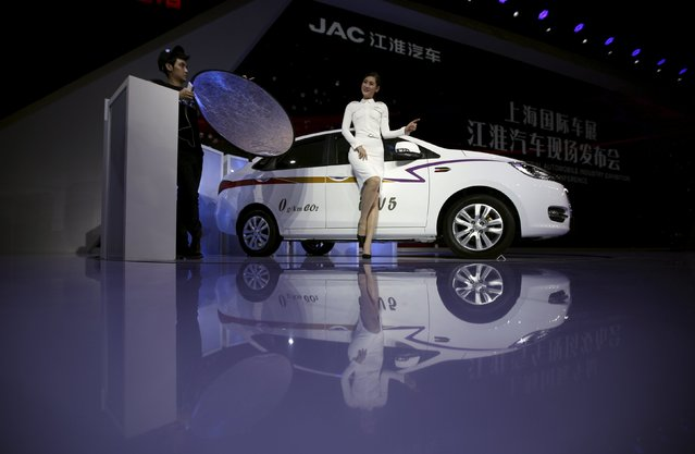 A model poses for pictures next to a JAC car during the 16th Shanghai International Automobile Industry Exhibition in Shanghai, April 20, 2015. (Photo by Carlos Barria/Reuters)