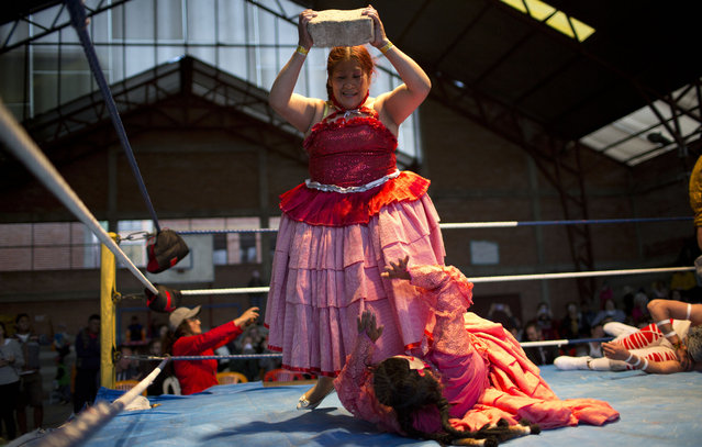 Veteran cholita wrestler Jennifer dos Caras, 45, holds a cement block over teen wrestler Lucero la Bonita in the ring in El Alto, Bolivia, Monday, January 21, 2019. Trainees of cholita wrestling are still a year away from their full professional debuts while competing in matches against established athletes. (Photo by Juan Karita/AP Photo)