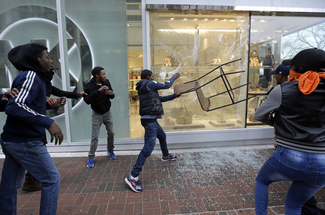 A protestor breaks a window at a store after a rally for Freddie Gray, Saturday, April 25, 2015, in Baltimore. (Photo by Patrick Semansky/AP Photo)