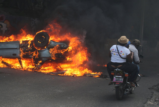 People on a motorcycle ride near a burning car during anti-government protests in Port-au-Prince, February 12, 2019. (Photo by Jeanty Junior Augustin/Reuters)