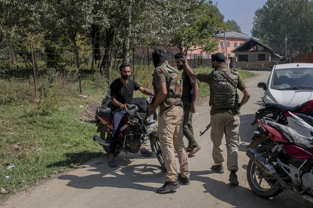 Indian policemen chase away Kashmiri motorcyclists as they cordon off the area outside a government school where two teachers were shot dead by assailants in the outskirts of Srinagar, Indian controlled Kashmir, Thursday, October 7, 2021. Authorities blamed militants fighting against Indian rule for the attack. Thursday's incident marks the seventh targeted killings in six days. (Photo by Dar Yasin/AP Photo)