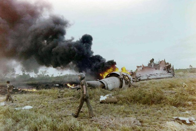 In this April 4, 1975 file photo, smoke rises from the wreckage of a U.S. Air Force C-5A transport plane after it crashed in a paddy field shortly after takeoff from the Saigon Airport, killing a large number of orphan children who were on board in a rescue flight from South Vietnam. (Photo by Dang Van Phuoc/AP Photo)