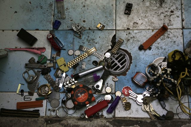In this April 9, 2015 photo, personal items left behind by transferred prisoners lay by a bathroom floor drain inside a prison cell at the now empty Garcia Moreno Prison, during a guided tour for the public in Quito, Ecuador. Also left behind were cuttings from newspapers or magazines of pinup girls, clothing, instruments, and images of Jesus Christ. (Photo by Dolores Ochoa/AP Photo)