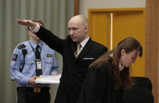 Anders Behring Breivik gestures as he enters a courtroom in Skien, Norway, on Tuesday, March 15, 2016. Breivik, the right-wing extremist who killed 77 people in bomb and gun attacks in 2011 arrived in court on Tuesday for his human rights case against the Norwegian government. (Photo by Lise Aserud, NTB scanpix via AP Photo)
