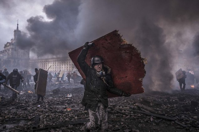 Protesters with improvised shields rush toward police lines in a sudden attack in Independence Square in Kiev, Ukraine, on February 20, 2014. Antigovernment protesters and riot police officers each used firearms on Thursday morning in renewed fighting over the square that began just after dawn, breaking a truce that had been declared just hours earlier. (Photo by Sergey Ponomarev/The New York Times)