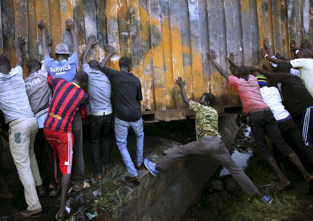 Protesters push a metal container to set up a barricade in Bujumbura, Burundi May 9, 2015. (Photo by Goran Tomasevic/Reuters)