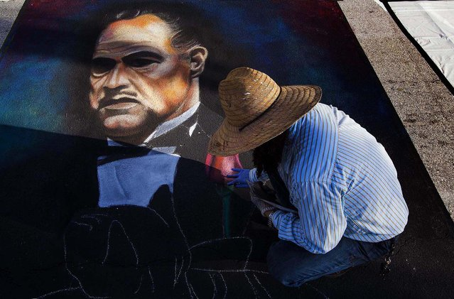 "Manuel Gomez, of West Palm Beach, works on a painting of Marlon Brando in ""The Godfather"". This is the eighth year Gomez has participated in the festival. (Photo by Mark Edelson/The Palm Beach Post)"