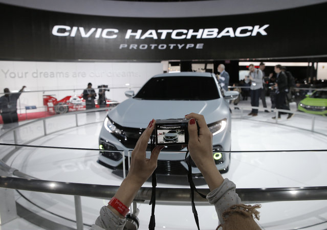 A woman takes a photo of the Honda Civic Hatchback Prototype vehicle during the media preview of the 2016 New York International Auto Show in Manhattan, New York on March 24, 2016. (Photo by Brendan McDermid/Reuters)