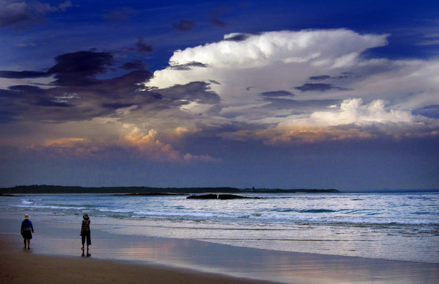 Storm clouds and dust can be seen in the sky above as people walk at dusk along Mollymook Beach, south of Sydney March 5, 2014. (Photo by David Gray/Reuters)