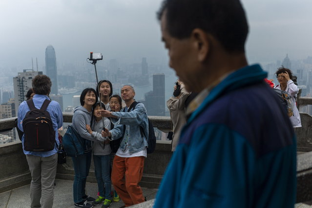 Tourists take photographs from a lookout on Victoria Peak in Hong Kong, China, 01 April 2019. Hong Kong is experiencing the northeast monsoon which is bringing cloudy weather with rain patches and fresh easterly winds. (Photo by Jerome Favre/EPA/EFE)
