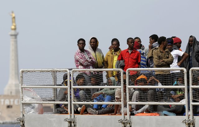 Migrants wait to disembark from the Migrant Offshore Aid Station (MOAS) ship MV Phoenix in the Sicilian harbour of Messina, Italy May 16, 2015. (Photo by Antonio Parrinello/Reuters)