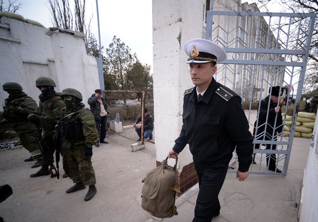 A Ukrainian officer leaves as Russian soldiers stand guard after they took control of the Ukrainian navy south headquarters base in Novoozerne on March 19, 2014. Russian forces seized control of a second Ukrainian navy base in western Crimea on March 19, hours after capturing the main navy headquarters in Sevastopol. Some 50 Ukrainian servicemen were seen filing out of the base at Novoozerne as Russian soldiers stood by, while pro-Moscow militants raised the Russian flag over the base. (Photo by Filippo Monteforte/AFP Photo)