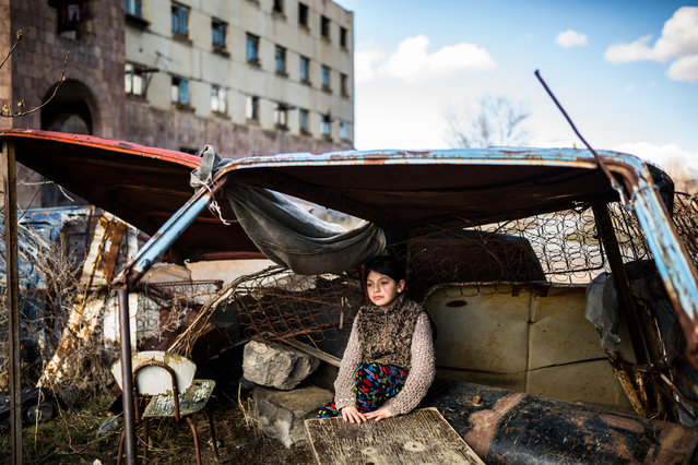"Daily life category, professional shortlist. ""Inhabitants of the empty"". Syuzanna sits in a shelter made from an old car in front of the abandoned building where she lives in Gyumri, Armenia. (Photo and caption by Yulia Grigoryants/2017 Sony World Photography Awards)"