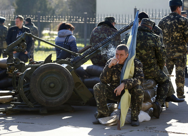 A Ukrainian serviceman holds a flag of Ukraine and smokes at a military base in the Crimean town of Belbek, near Sevastopol March 22, 2014. Russian troops have surrounded the Ukrainian airbase in Crimea and issued an ultimatum to forces inside to surrender, the deputy commander of the base in Belbek, near Sevastopol, said on Saturday. (Photo by Shamil Zhumatov/Reuters)