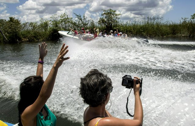 In this May 13, 2019 photo, tourists take photos while being transported by boat to the Laguna del Tesoro, in the Zapata Peninsula, Matanzas, Cuba. The U.S. has prohibited Americans from patronizing a series of hotels and other facilities run by the military conglomerate that controls many of the most important sectors of the Cuban economy. (Photo by Ismael Francisco/AP Photo)