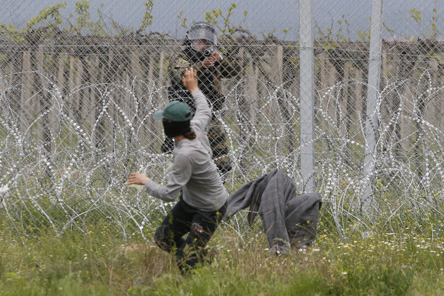 A migrant man trying to remove barbed wire along the fence clashes with Macedonian police at the northern Greek border point of Idomeni, Greece, Wednesday, April 13, 2016. New clashes have broken out between Macedonian police and stranded refugees and other migrants trying to scale a fence on Greece's border with the country. (Photo by Amel Emric/AP Photo)