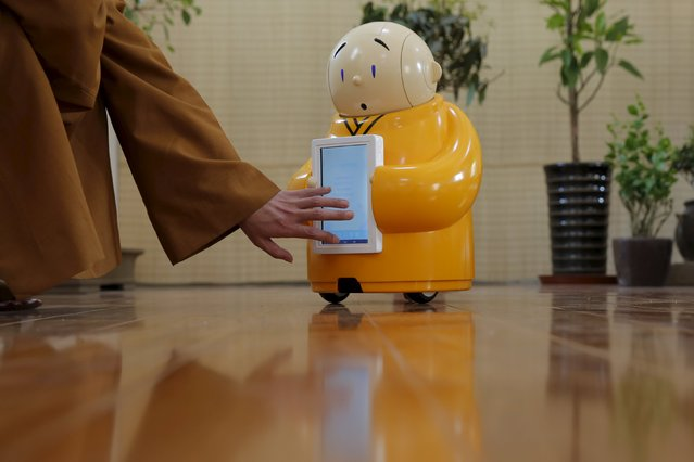 Master Xianfan touches a screen on robot Xian'er as he demonstrates the robot's conversation function during a photo opportunity in Longquan Buddhist temple on the outskirts of Beijing, April 20, 2016. (Photo by Kim Kyung-Hoon/Reuters)