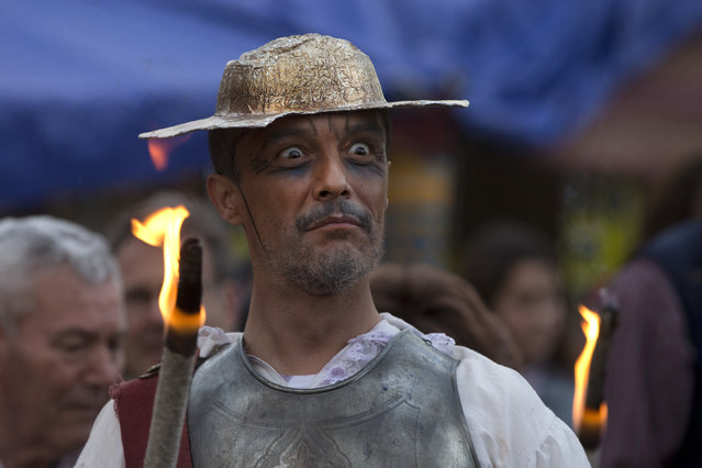 """A man dressed as the character of Don Quixote holds a flaming stick during a mock funeral for Spanish writer Miguel de Cervantes, author of """"Don Quixote"""" to commemorate the 400th anniversary of his death, in his birthplace of Alcala de Henares, Spain, Friday April 22, 2016. (Photo by Paul White/AP Photo)"""