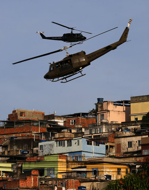 Police helicopters fly over the Mare slums complex in Rio de Janeiro March 30, 2014.The federal troops and police occupied the Mare slums complex on Sunday to help quell a surge in violent crime following attacks by drug traffickers on police posts in three slums on the north side of the city, government officials said. (Photo by Ricardo Moraes/Reuters)