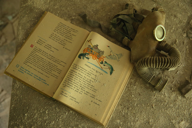 A schoolbook lies on a pupils' desk next to a Cold War-era gas mask in a classroom of abandoned School Number 3 on September 30, 2015 in Pripyat, Ukraine. (Photo by Sean Gallup/Getty Images)