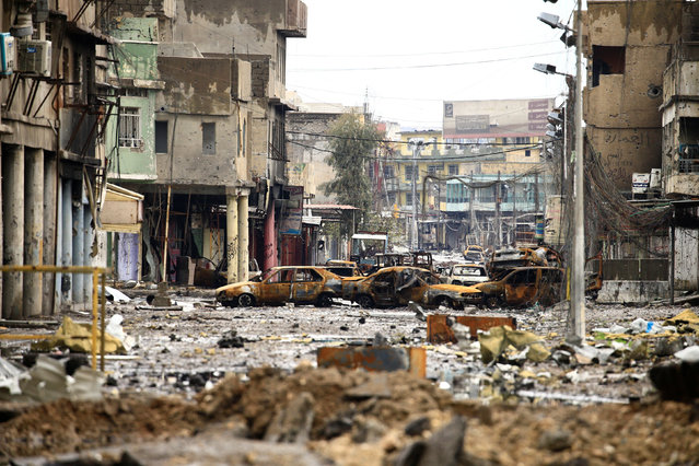 Cars burnt and destroyed by clashes are seen on a street during a battle between Iraqi forces and Islamic State militants, in Mosul, Iraq March 16, 2017. (Photo by Thaier Al-Sudani/Reuters)
