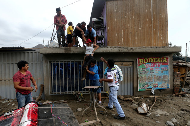 People help a woman get off the roof of a house after a massive landslide and flood in the Huachipa district of Lima on March 18, 2017. (Photo by Guadalupe Pardo/Reuters)