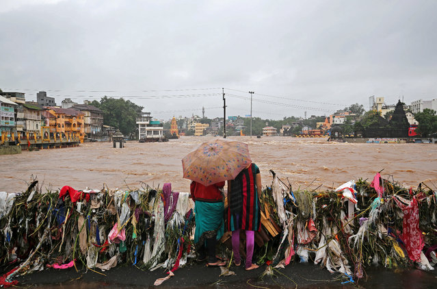Women watch submerged temples and houses from a bridge covered with garbage by the waters of overflowing river Godavari after heavy rainfall in Nashik, India, August 5, 2019. (Photo by Francis Mascarenhas/Reuters)