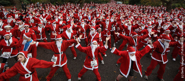 Charity runners dressed as Santa Claus warm up before taking part in the Disability Snowport UK fun run in Battersea Park