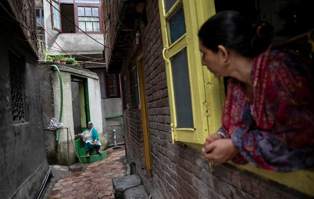 A Kashmiri woman talks to another in an alley during restrictions after the scrapping of the special constitutional status for Kashmir by the government, in Srinagar, August 14, 2019. (Photo by Danish Siddiqui/Reuters)