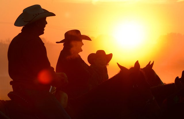 Worshippers join together for a sunrise service at the No Fences Cowboy Church Easter Sunday, April 20, 2014 in Falkville, Alabama. Cowboys on horseback greet the sunrise and arriving worshippers. (Photo by Gary Cosby Jr./AP Photo/The Decatur Daily)