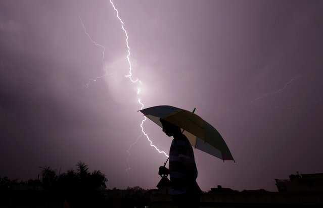 A pedestrian walks with an umbrella as lightning strikes during an evening thunderstorm in Jammu, India on May 14, 2015. (Photo by Rakesh Bakshi/AFP Photo)