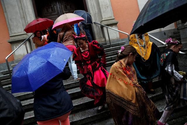 """Maya"" girls and their assistants leave San Lorenzo church in the rain during ""Las Mayas"" festivity in Madrid, Spain, May 8, 2016. (Photo by Susana Vera/Reuters)"