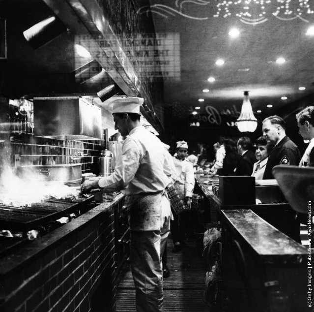 1965:  As customers queue up, cooks broil steaks on the charcoal pits at Tad's Steak House in Times Square, New York City